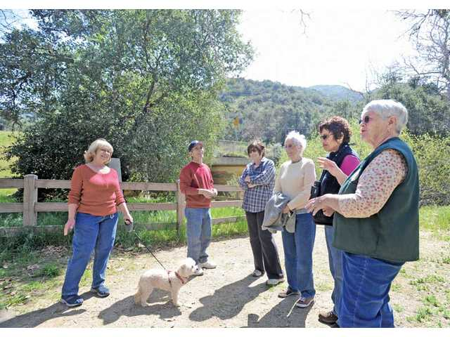 Volunteer naturalist Judy McClure, right, tells the story of gold being found at the site of the Oak of the Golden Dream on March 9, 1842, to a small group who took the guided nature tour at the Placerita Canyon Nature Center in Santa Clarita on Saturday.