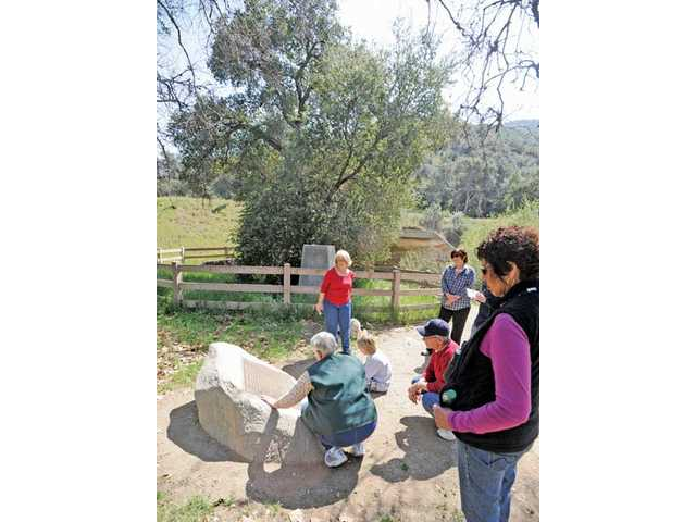 Volunteer naturalist Judy McClure, kneeling, reads the story from the memorial plaque of gold being found at the site of the Oak of the Golden Dream on March 9, 1842, to a small group who took the guided nature tour at the Placerita Canyon Nature Center in Santa Clarita on Saturday.