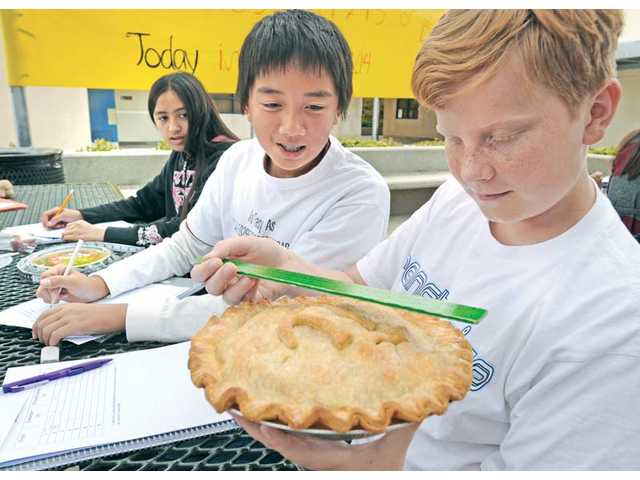Rancho Pico Junior High School eighth-graders Jason Taw-Say, middle, and Michael Petras, right, measure the diameter of an apple pie Michael and his mother baked for Pi Day on Monday. The students' at the Stevenson Ranch school were assigned the task of using existing math skills to visualize how pi works to find the circumference of a circle.