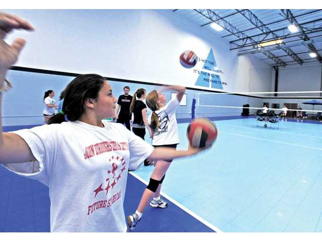 Adela Martinez, 12, practices her serve with the Legacy Volleyball Club's 13-1 team in the 19,000-square-foot Legacy Volleyball facility in Valencia on Friday.