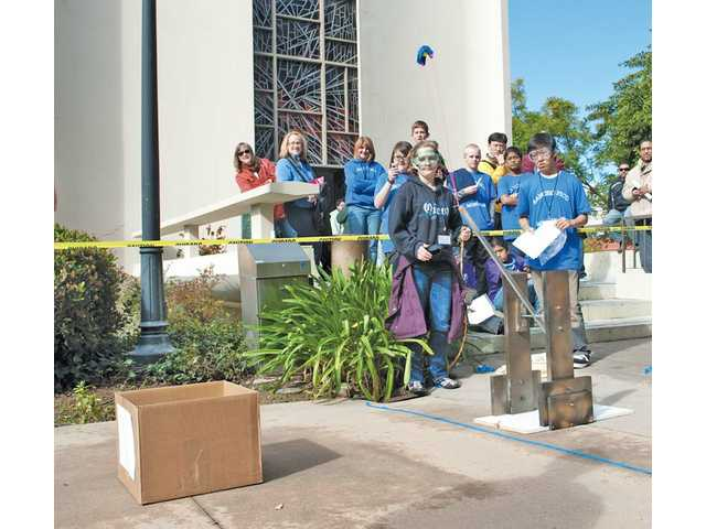 Students from Rancho Pico Junior High School test one of their science projects during the recent Los Angeles Regional Science Olympiad competition at Occidental College. The students are trying to launch objects into the cardboard box at left.