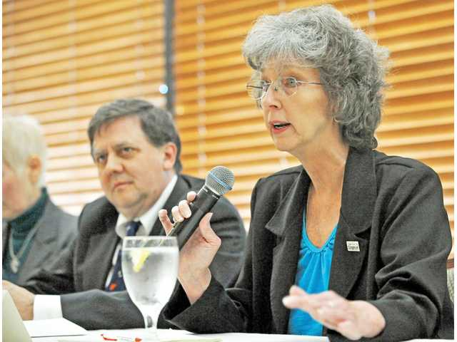 Lila Littlejohn, The Signal's executive editor, right, speaks as Signal reporter Jim Holt, left, listens during a water-chloride panel sponsored by the Valley Industry Association at the organization's monthly membership luncheon Tuesday.