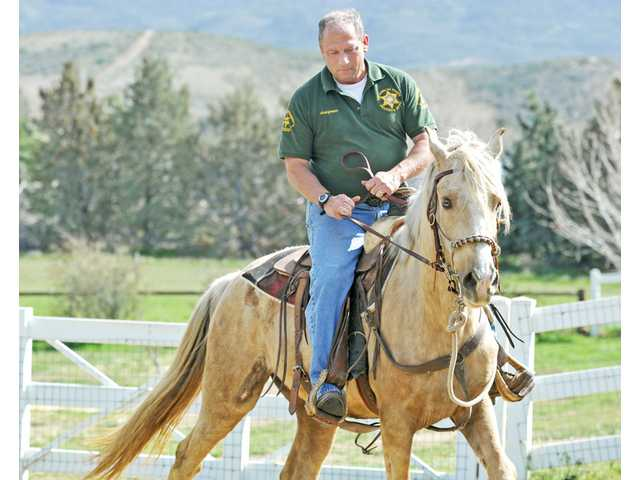 Sgt. John Hargraves is training The Dude, a palomino gelding, for mounted enforcement work with the Los Angeles County Sheriff's Department. They are seen at Hargraves' home in Leona Valley on Thursday.