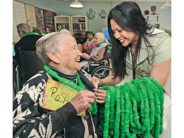 Resident Rosalia Cianessi, left, gets a green necklace from hospital activities director Mila Mercader during the Santa Clarita Convalescent Hospital's St. Patrick's Day celebration in Newhall.