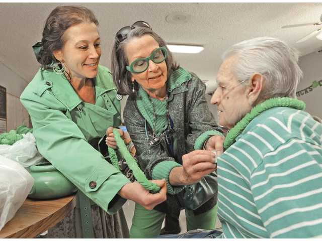 "Resident Jim Thornton, right, gets a green necklace and a ""Kiss me I'm Irish"" button from activities volunteer Erin Doherty, left, and her mother, Melinda Doherty-Gordon, during the Santa Clarita Convalescent Hospital's  St. Patrick's Day celebration in Newhall on Thursday."