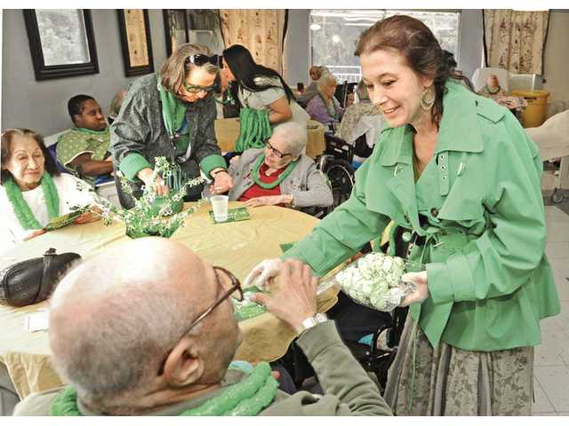 Doherty, right, and Doherty-Gordon, standing left,  hand out cookies with green frosting to the residents of Santa Clarita Convalescent Hospital during its St. Patrick's Day celebration in Newhall on Thursday.
