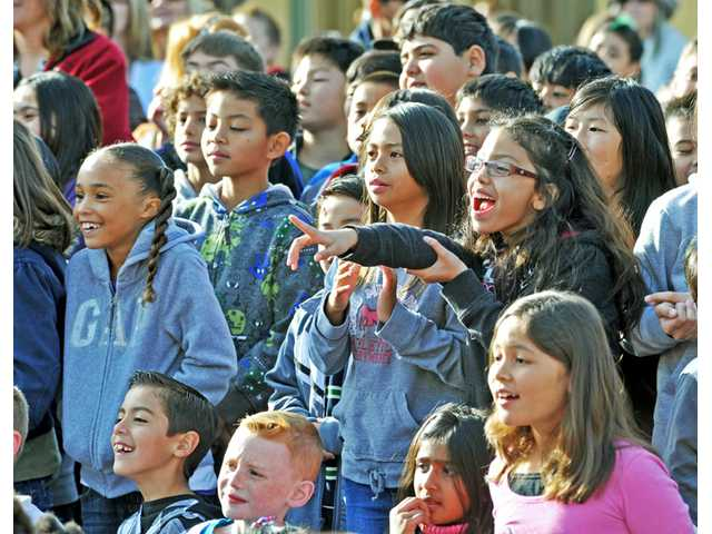 Students react as a pair of pot-bellied pigs is brought out at an assembly at Fair Oaks Ranch Community School in Canyon Country on Friday. Assistant principal Alan Reinstein offered to kiss a pair of pigs at an assembly after students met the challenge of reading 12,000 books or 150 million words as part of the school's Accelerated Reader program.