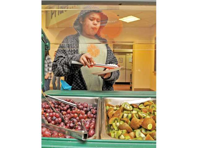 Fifth-grader Angel Jacobo, 11, serves up a plate of grapes and kiwi.