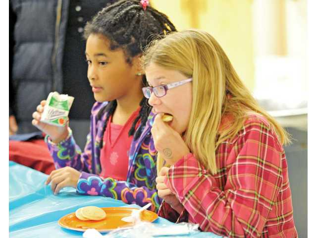 Fourth-graders Sabrina Maldonado, 10, left, and Nicole Loughnane, 9, enjoy pancakes.
