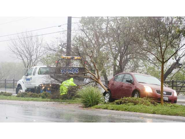 Dennis Hancock of Wolf's Towing prepares to tow a Nissan sedan that hit a tree on the median of Soledad Canyon Road about a half-mile east of Bouquet Canyon Road in Santa Clarita on Sunday. Heavy rains and high winds contributed to collapsed rooftops, auto crashes and toppled trees in the Santa Clarita Valley.
