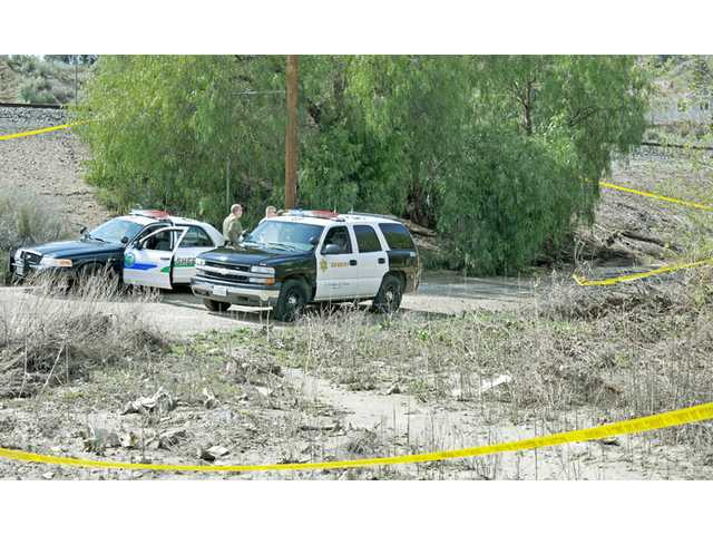 Los Angeles County sheriff's deputies set up crime-scene tape around an area where a body was found in a ravine near Soledad Canyon Road, west of Camp Plenty Road, in Canyon Country on Tuesday.