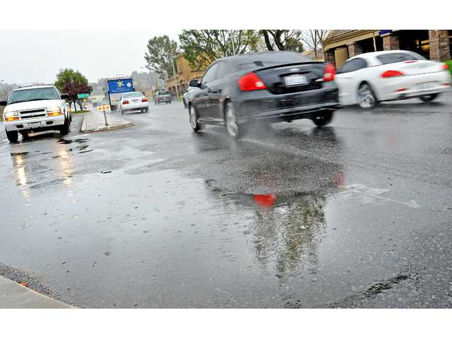 Rain falls on a puddle as traffic flows on Bouquet Canyon Road, near the Bouquet Center shopping center, in Saugus on Wednesday. See A2 for local weather report.