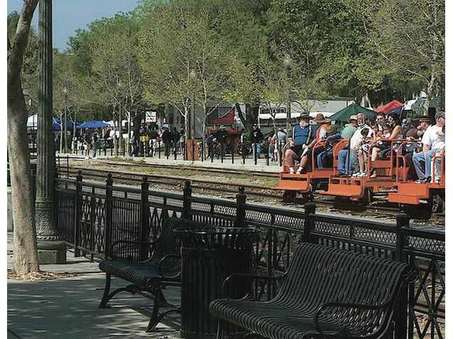 At a previous Railfest, attendees ride a 'speeder' past some of the many vendor booths present.