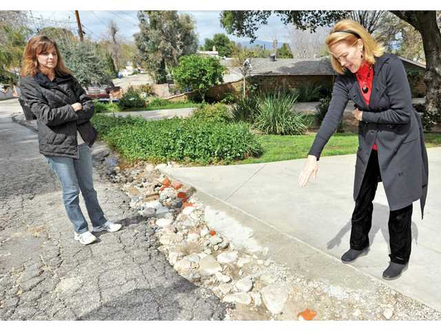 Chris Amundson, left, and Michelle Crawford point out damage on De Wolfe Road in Newhall on Thursday. Some residents on the private road seek help from the city of Santa Clarita to repair the damage. City officials contend the road is the homeowners' responsibility because it's private.
