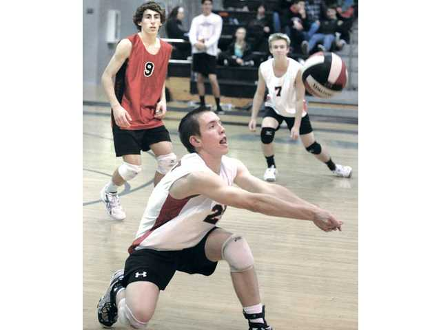 Hart's Chris Leclair, front, digs a shot from La Canada as Loy Mueller (9) and Jared Turner (7) look on Friday at Hart.