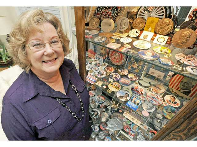 Pat Hobbs stands alongside some of the more than 20,000 pieces of political memorabilia that she and her husband, Max, have collected in her Canyon Country home.