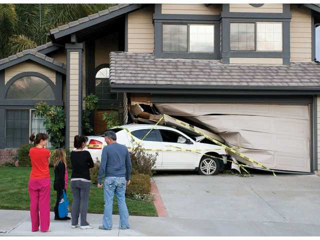 Yaron Cohen, right, speaks with homeowner Frances Cohen, second from right, about the car that crashed into her house on the corner of Kenton Lane and Copper Hill Drive in Saugus, while Frances Cohen's daughters, Elizabeth Santiso, 24, left and Sivon Cohen, 9, look on. The car hit the house around 3 a.m. Sunday but could not be removed easily due to the amount of structural damage to the house.