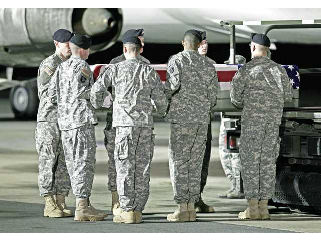 Chaplain Capt. Richard J. Dunbar, left, reads a prayer over the transfer cases containing the remains of Army Cpl. Donald R. Mickler Jr. of Bucyrus, Ohio, and Army Specialist Rudy A. Acosta of Canyon Country, Calif. upon arrival at Dover Air Force Base, Del. on Sunday, March 20.