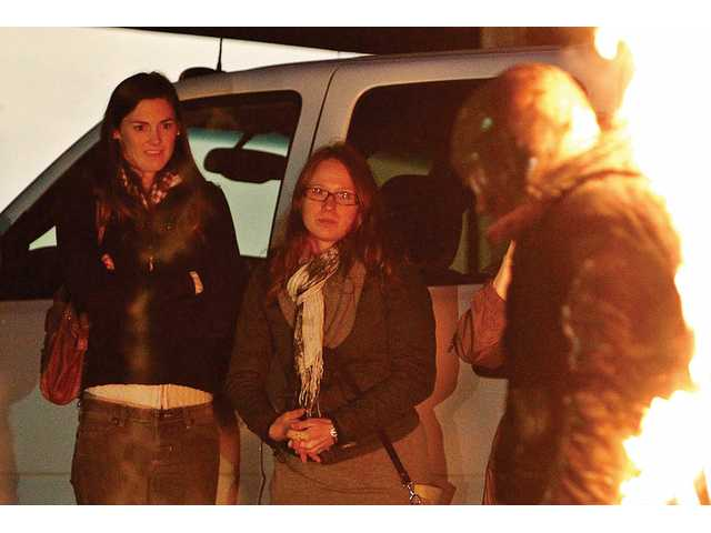 Ivy Brown, left, and Sarah Gyldenvand watch as stuntman Jayson Dumenigo walks past them while lit on fire in the parking lot of Action Factory, Dumenigo's business in Canyon Country on Sunday. Dumenigo kept his body in flames for five minutes and 26 seconds in order to break a Guinness World Record for a full-body burn without oxygen.