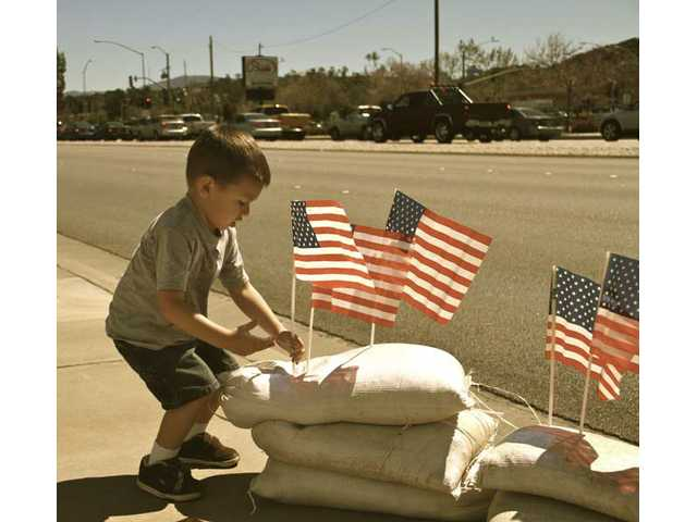 Three-year-old Jordan Blankenship came all the way from Lake Elsinore to help his uncle, Darrell Sanders, set up flags on Soledad Canyon Road for Spc. Acosta's funeral Thursday afternoon.