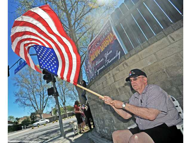 Glen Sherman, 82, of Valencia, waves an American flag prior to the arrival of the funeral procession of Army Spc. Rudy A. Acosta on Orchard Village Road at Mill Valley Road in Santa Clarita.