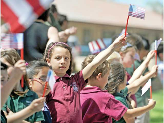 Nadia Natour, 6, waves an American flag in front of Pinecrest School during the funeral procession for Spc. Rudy A. Acosta on Thursday.