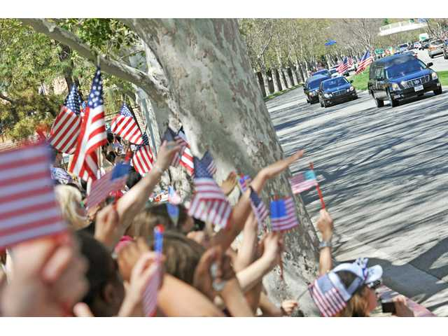 Schoolchildren carry American flags as the hearse bearing the body of Army Spc. Rudy A. Acosta is driven in front of Pinecrest School in Santa Clarita on Thursday. Hundreds lined the route waving American flags to support Acosta's family.