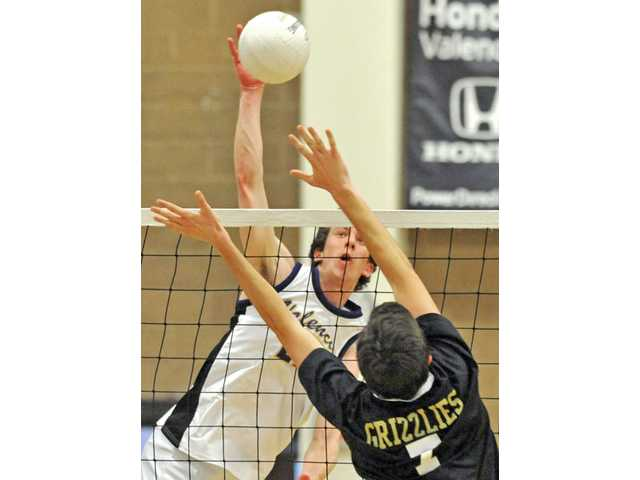 Valencia outside hitter Broc Oppler, back, attempts a kill against Golden Valley's Alec Schlossman on Thursday at Golden Valley High School. Oppler finished with 22 kills.