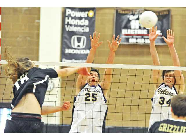 Golden Valley's Andrew Raulinaitis, left, attempts a kill as Valencia's Shane Nazarian (25) and Daniel Salovich (34) try to block on Thursday at Golden Valley. The Vikings won 3-1.
