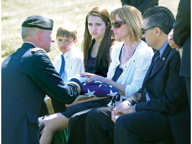 Brig. Gen. Gregg C. Potter, left, presents the flag from the casket of Spc. Rudy A. Acosta to Acosta's family, from left, his brother Doran, 10; his sister Allie, 15; his mom, Carolyn, receiving flag; and his father, Dante, at graveside services held at Eternal Valley on Thursday.