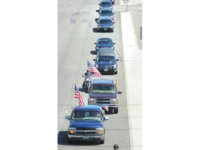 Hundreds of cars follow the hearse, center, carrying the body of Spc. Rudy A. Acosta as the funeral procession passes under the Golden Valley overpass on Thursday.