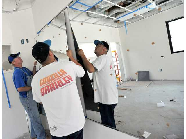 Mark Adams, left, and Marco Castillo of Sauer Glass & Mirror place a mirror in the fire station's exercise room.