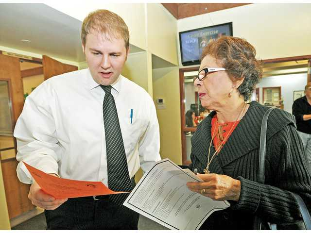 Patrick Bryant, administrative analyst for Santa Clarita, left, goes over forms for the city's Senior Transit Ambassador program with Carmen Cuadros, of Valencia, at the Santa Clarita Valley Senior Center in Newhall on Wednesday.