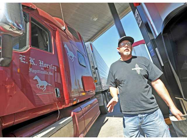 David Rule, 49, of Griffin, Ga., speaks about his experiences on the road while taking a break at a Castaic truck stop on Monday. Rule hauls produce and poultry between several points on a route between Georgia and California.