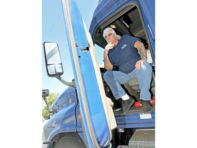 Joseph Norman, 59, a truck driver for a U.S. Postal Service contractor, relates his road experiences while taking a break at a truck stop in Castaic on Monday.