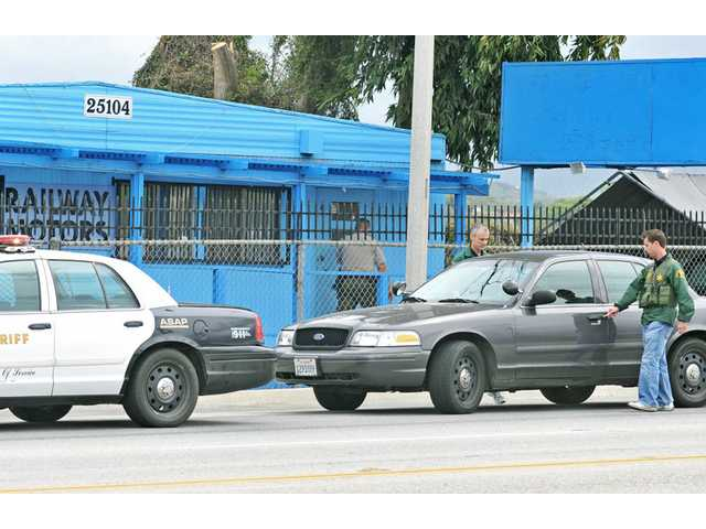 Los Angeles County sheriff's investigators leave the scene of an armed robbery at Railway Motors, at 25104 Railroad Ave. in Newhall, on Thursday.