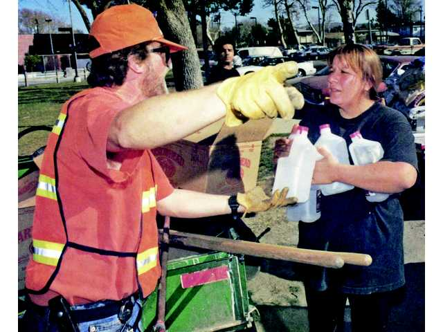 City employee Michael Marks, left, hands out water and instructions to Newhall resident Lupe Munguia in the days following the Jan. 17, 1994, Northridge Earthquake. Scientists in 2008 forecast a 99-percent chance of an equally large quake hitting Southern California.