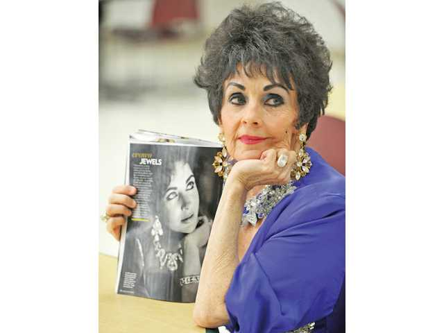 Nancy Casey, 70, poses alongside a 1959 photo of Elizabeth Taylor published in the April 11, 2011, issue of People magazine at Bouquet Canyon Senior Apartments in Saugus on Wednesday.