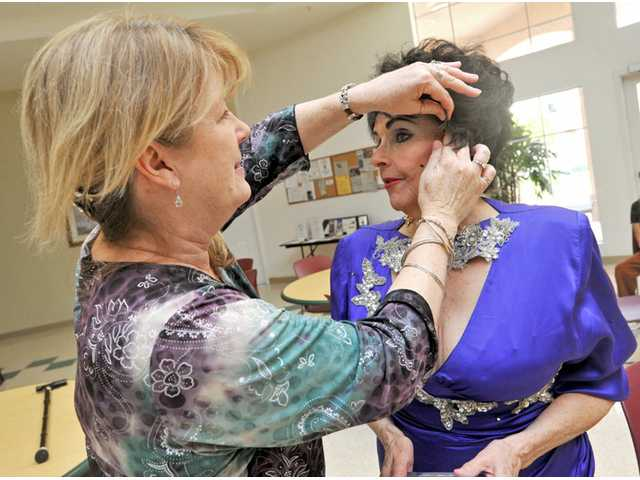 Volunteer Kim Wells, 54, left, fixes up Nancy Casey's hair at Bouquet Canyon Senior Apartments in Saugus on Wednesday. Casey said comparisons to Elizabeth Taylor began when Casey was in high school.