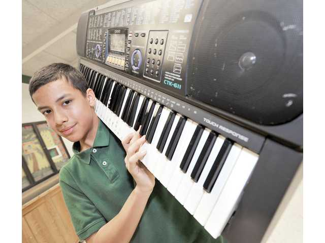 Carlos Vasquez, 13, holds a Casio keyboard in the teen room of the Boys & Girls Club of Santa Clarita Valley in Newhall on April 1. The keyboard is one of a few instruments that he has practiced since he taught himself how to play the piano in 2008.