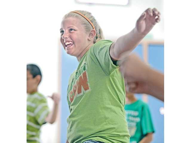"Haily Taylor works out with three classes of fifth-graders during an intense, 30-minute aerobic work out at Pinetree Community School in Canyon Country on April 1. The students attend this ""boot camp"" each week as part of the schools fitness curriculum that also includes yoga and martial arts. About 74 percent of the school's fifth-grade students in 2009-10 were considered in the healthy fitness zone, according to state data."
