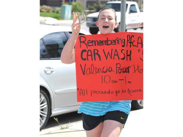 Santa Clarita Christian School student Juliette Valaer, 17, cheers on the corner of Magic Mountain Parkway and Valencia Boulevard as a passing motorist stops to give a $5 donation in support of the school's car wash fundraiser benefiting the family of U.S. Army Spc. Rudy A. Acosta.