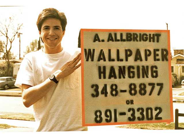 Joshua Abramson, owner of A. Allbright Painting, holds up the first advertisement he created for the first day of his business. This photo of a 19-year-old Abramson was taken by a girlfriend who is now his wife. Abramson said he will use A. Allbright Painting to give work opportunities to young people to repay the time others have invested in him when he was a teenager.