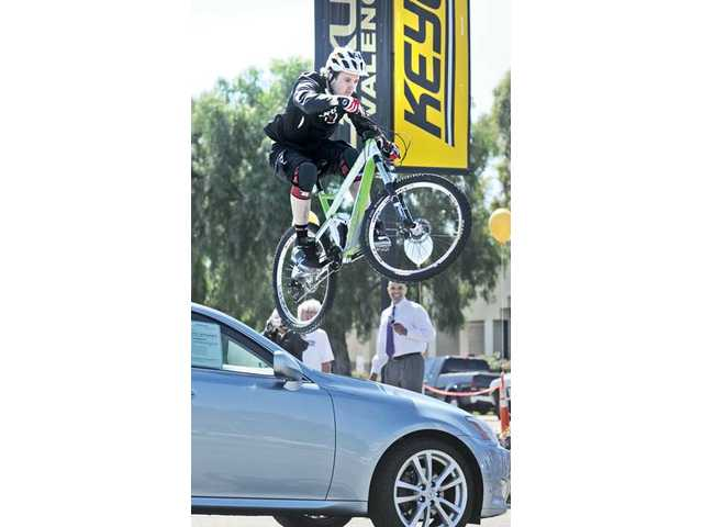 Professional mountain bike rider Aaron Chase jumps over the hood of a new Lexus car during the event.