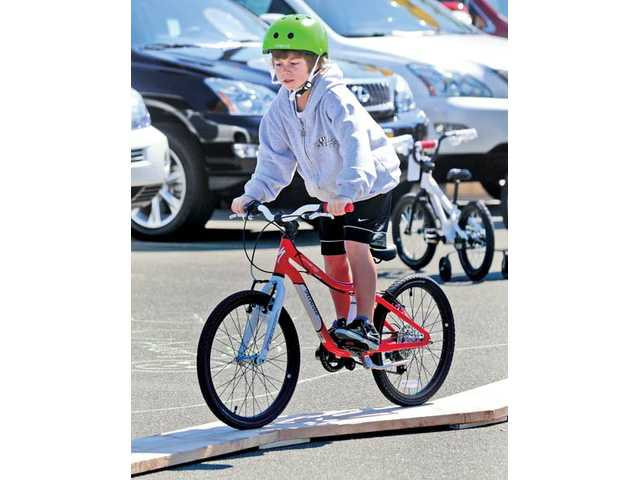 Jake Biscailuz, 10, of Valencia, balances his bike on a board ramp during a bike-safety event held at Lexus of Valencia in Valencia on Saturday.