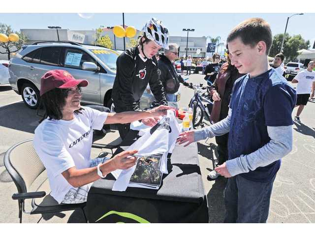 "Champion mountain bike racer David ""Tinker"" Juarez, left, and professional mountain bike rider Aaron Chase, center, of Cannondale Bicycles  sign T-shirts for Garrett Stover, 12, during a bike-safety event held at Lexus of Valencia in Valencia on Saturday."