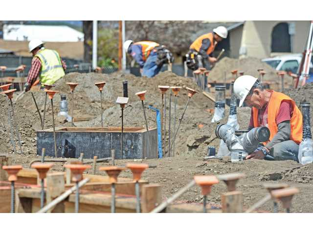 Plastic safety caps top rebar reinforcement as workers prepare footing forms that will support the concrete foundation of the Newhall Library on Lyons Avenue in Newhall on Friday.