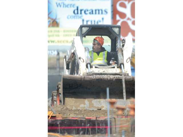 "The words ""Where Dreams Come True"" are seen on a billboard behind a loader as it moves dirt on the construction site of the Newhall Library on Friday."