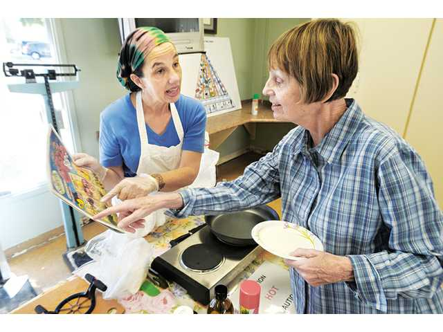 Correnti, left, discusses ingredients with Anny Fry as she prepares the salad. The class was part of an eight-week series that offers two classes every Friday, at 1 and 2:30 p.m. The free sessions focus on cooking and eating healthy as a senior.