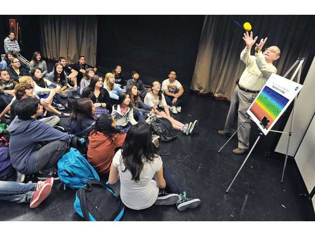 Jet Propulsion Laboratory Project Manager Ben Parvin, right, catches a sound-emitting ball thrown over the heads of seventh- and eight-graders at Arroyo Seco Junior High School in Valencia on Wednesday. The demonstration taught students about the changing sound frequencies of the Doppler effect as sounds change position.